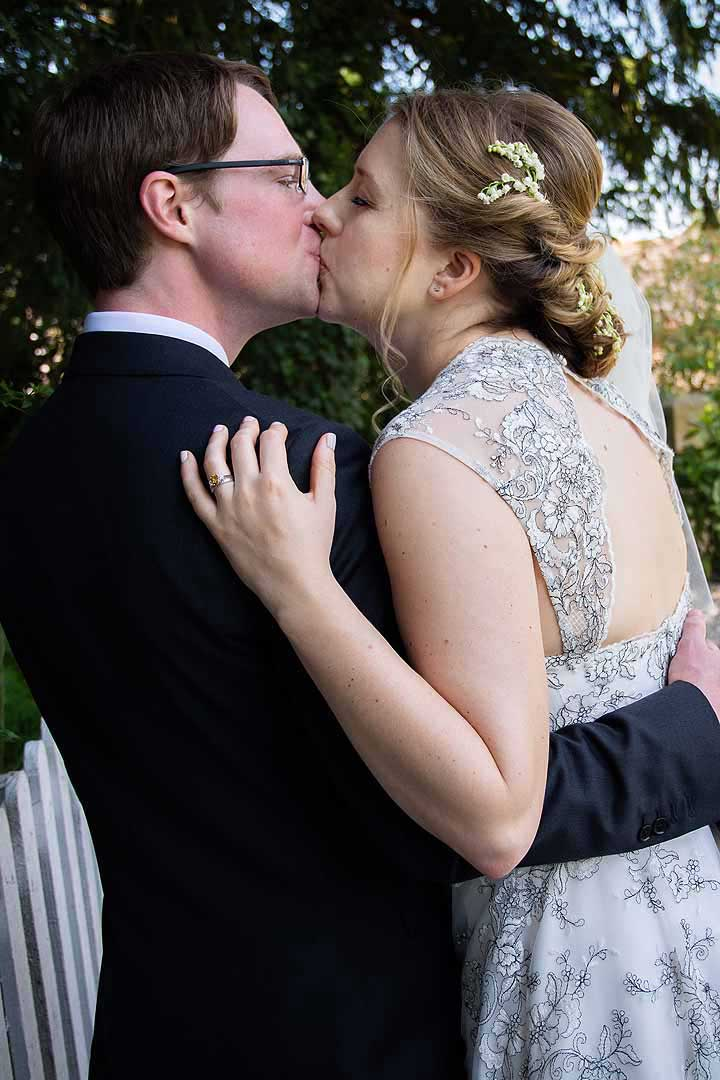 bride and groom kiss in a garden