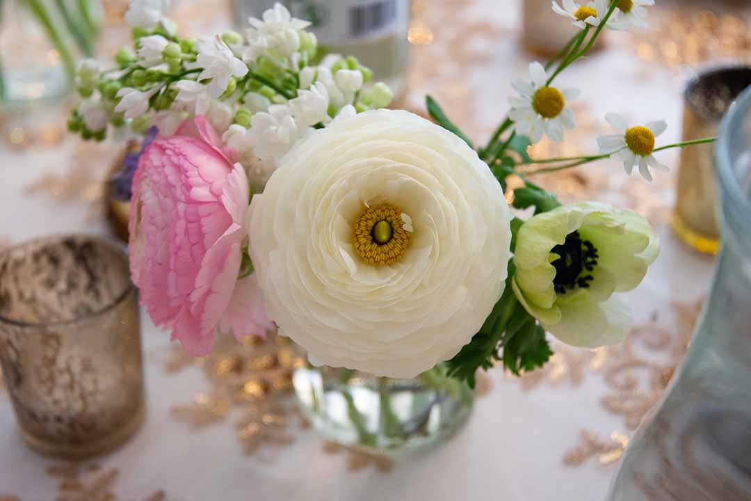 white and pink flowers in a jar on a table