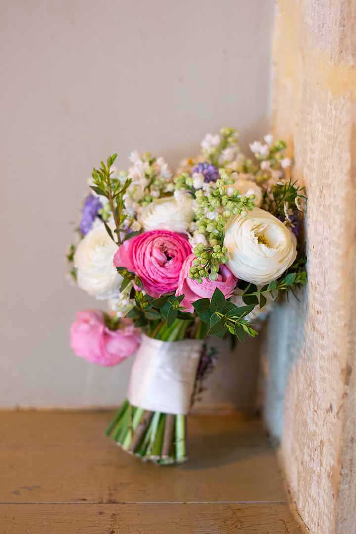 pink white and blue wedding bouquet propped up by a wall