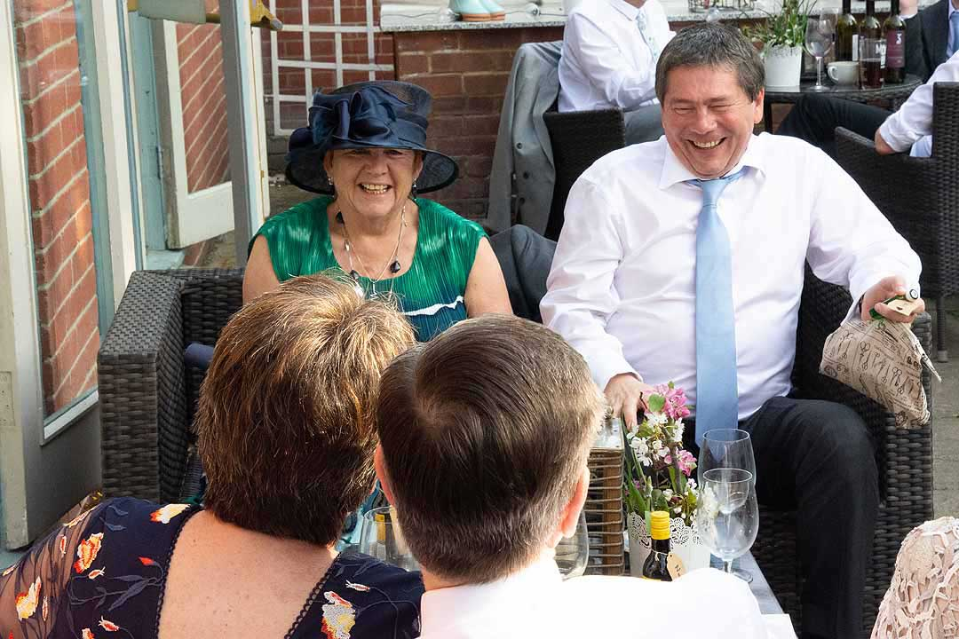 lady in a blue hat and man with a blue tie laughing