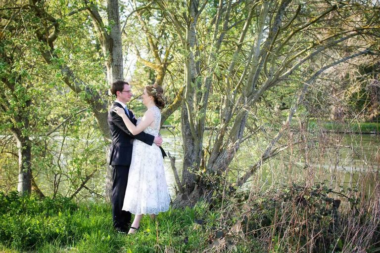 bride and groom embracing in the shade of trees
