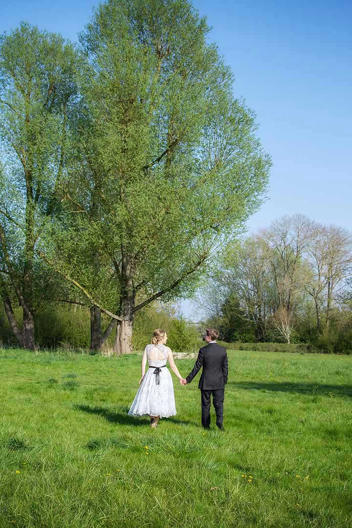 bride and groom walking in a park with grass, tall trees and blue skies