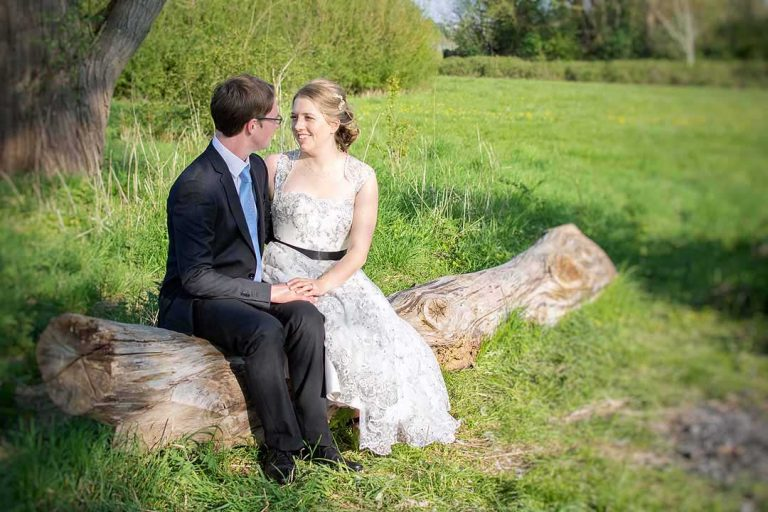 bride and groom sitting on a log in the sunshine and looking at each other