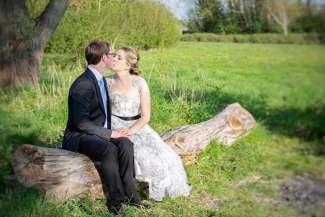 bride and groom sitting on a log kissing