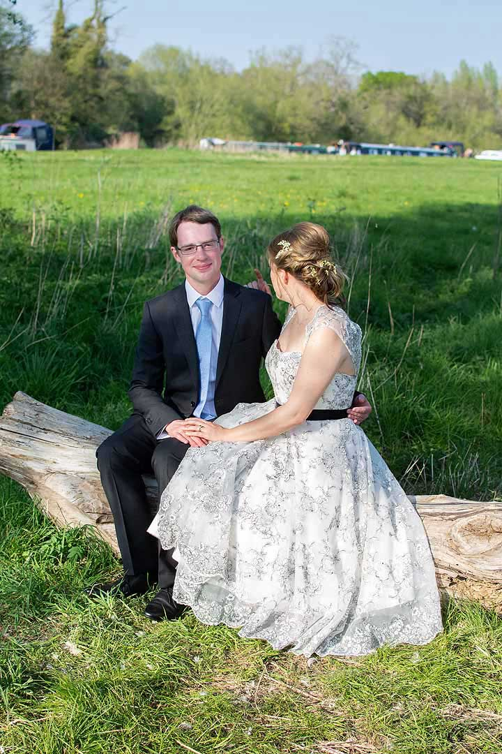 bride and groom sitting on a log in the sunshine