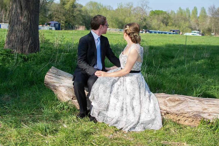 bride and groom sitting on a log and looking into the distance
