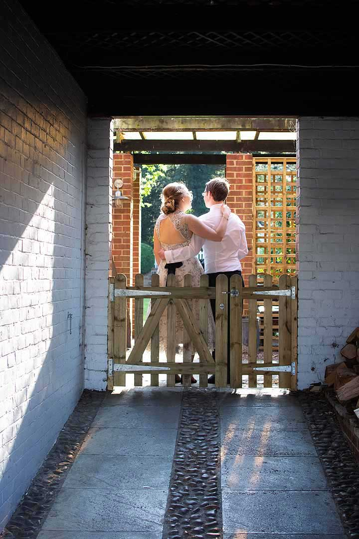 bride and groom with arms around each other in a sunny archway