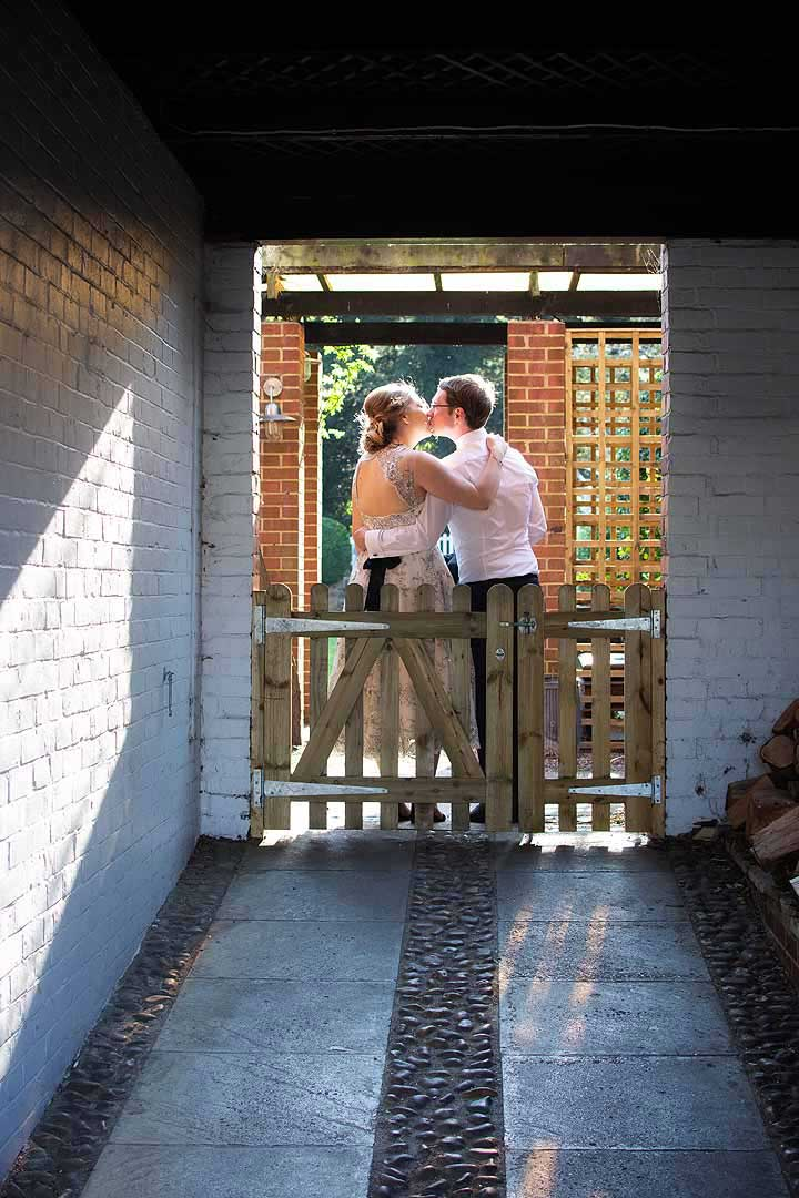 couple kissing in an archway the other side of a wooden gate