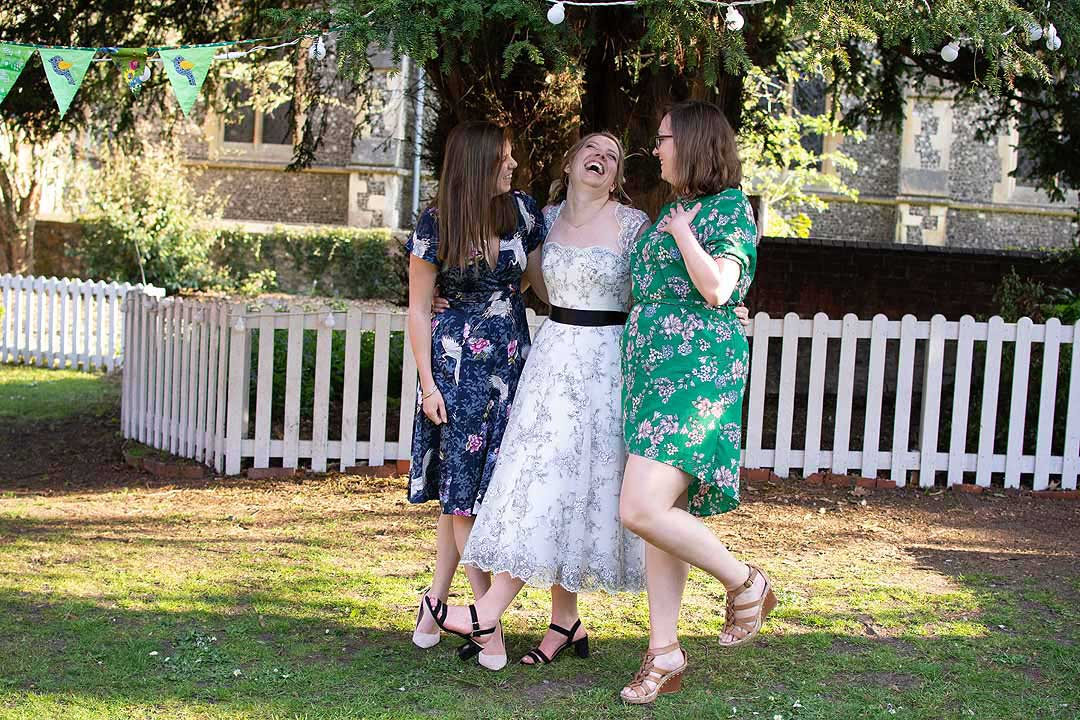 bride and two friends laughing in a garden