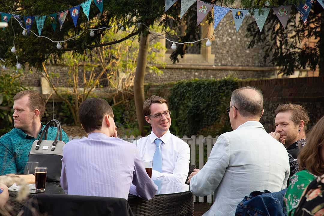 groom chating with friends in a garden
