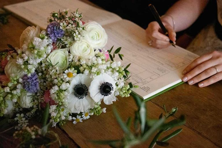bride signing the marriage register with bouquet