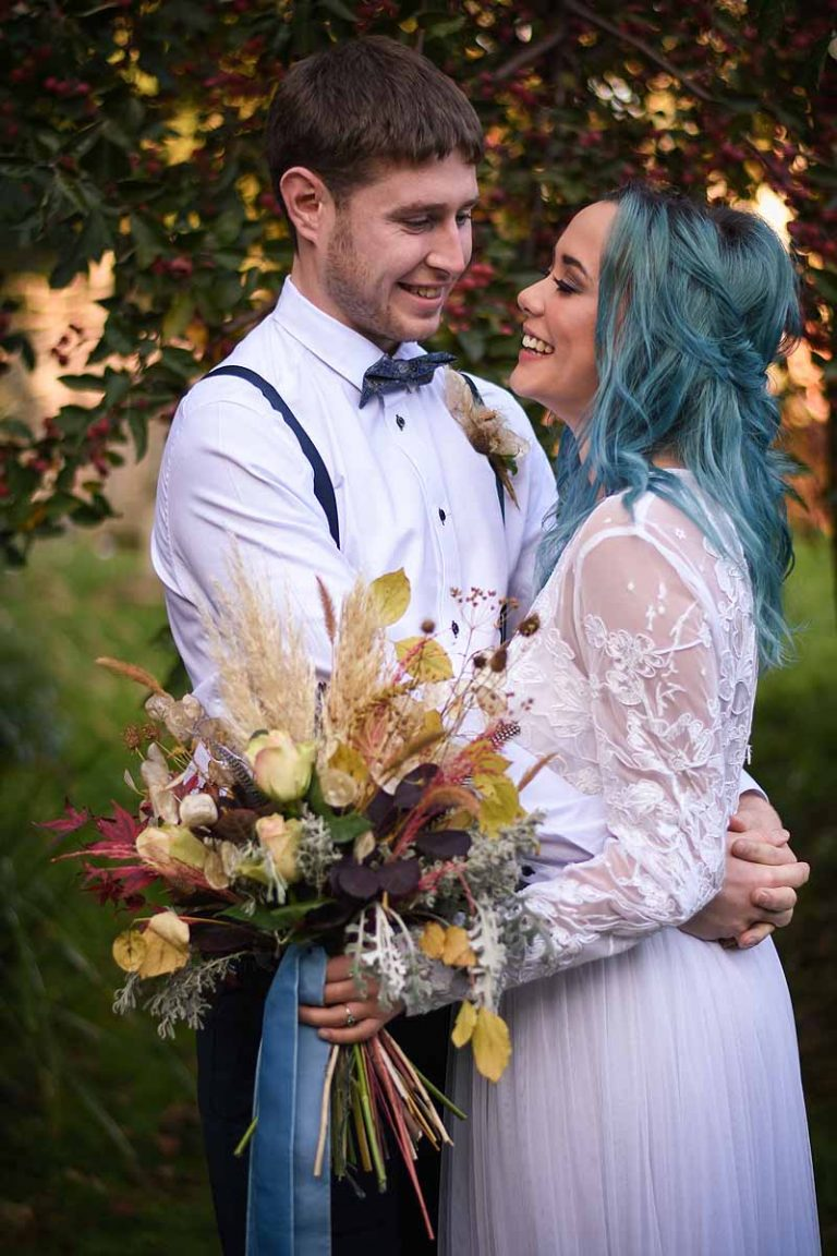 Bride with blue hair and groom in a garden in autumn