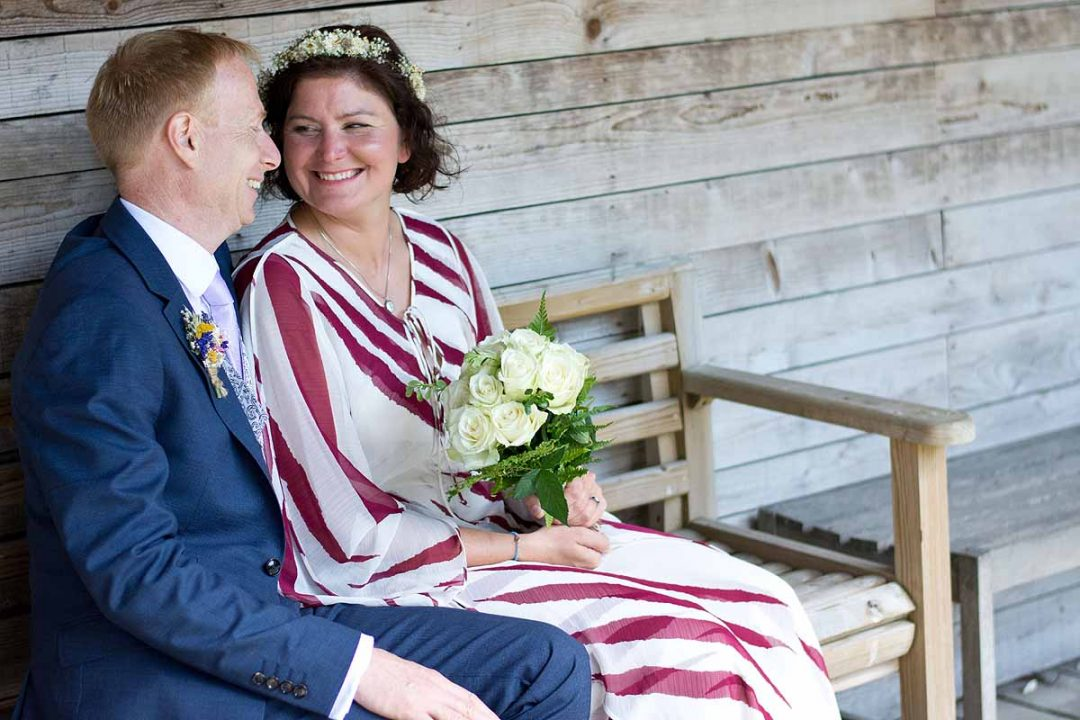 bride and groom sat on a wooden bench