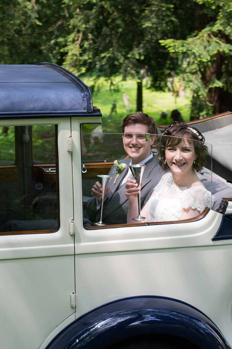 bride and groom raising champagne glasses in a classic car