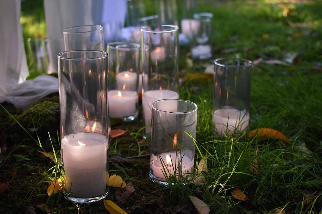 candles in glasses on the grass