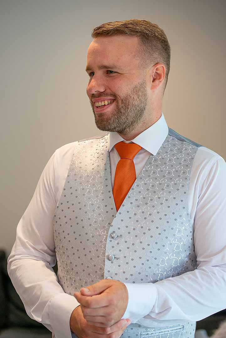 groom in a grey waistcoat and orange tie