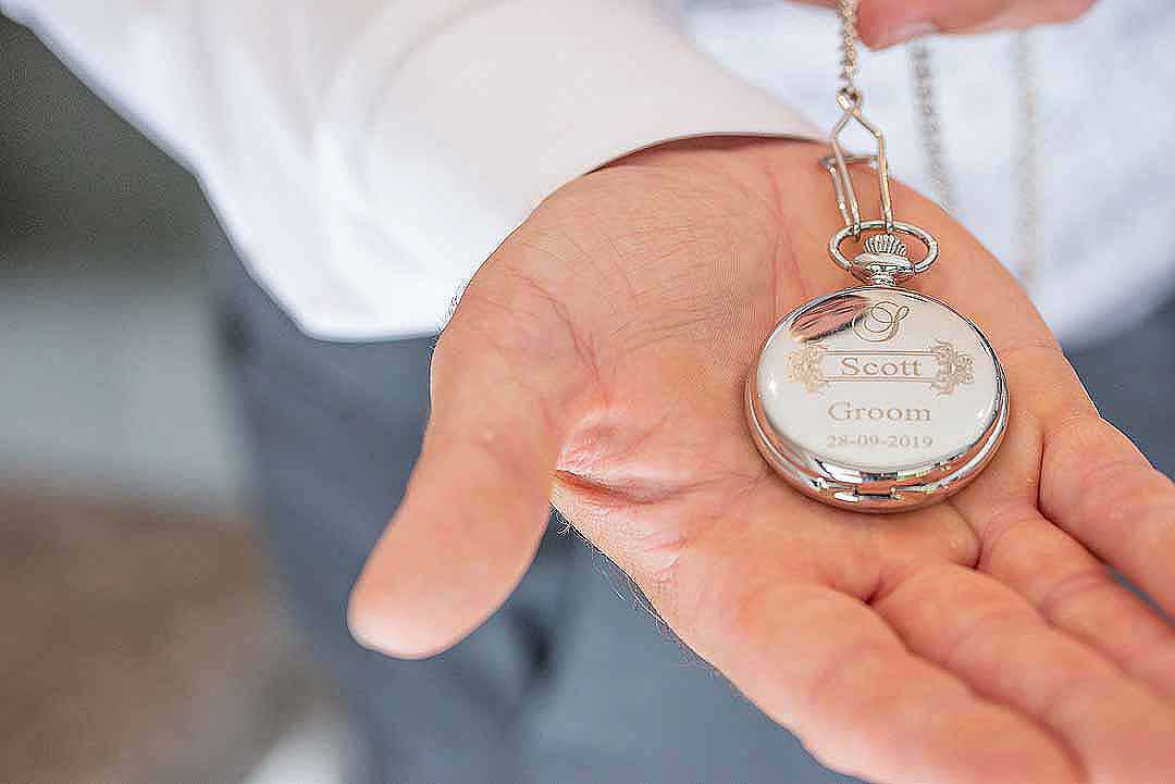 Scott the groom's pocket watch in the palm of his hand
