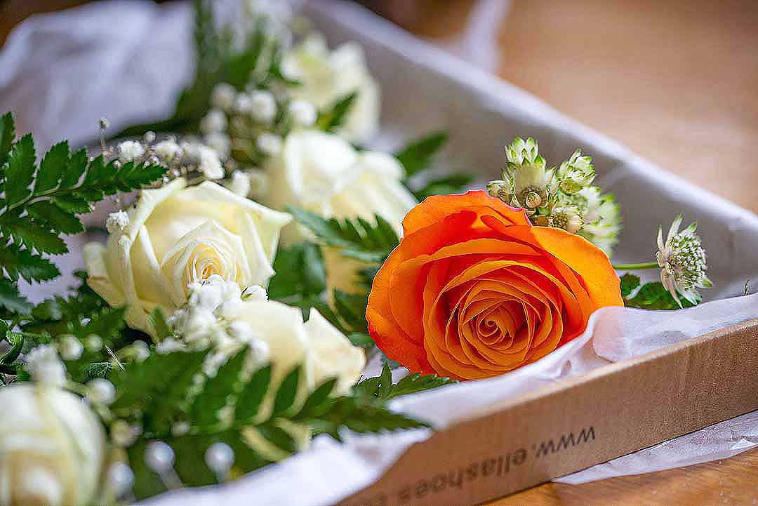 orange and white rose buttonholes in a box