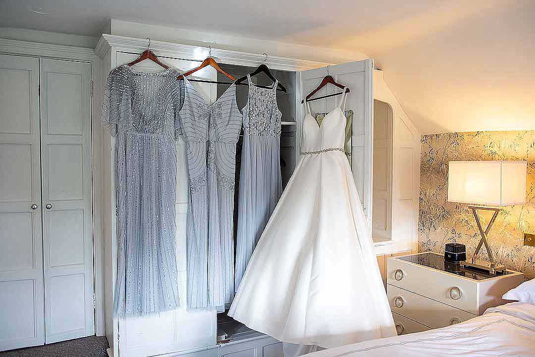 bridal gown and bridesmaid dresses on hangers