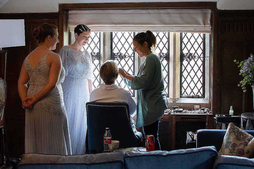 mother of the bride having her makeup done while bridesmaids look on