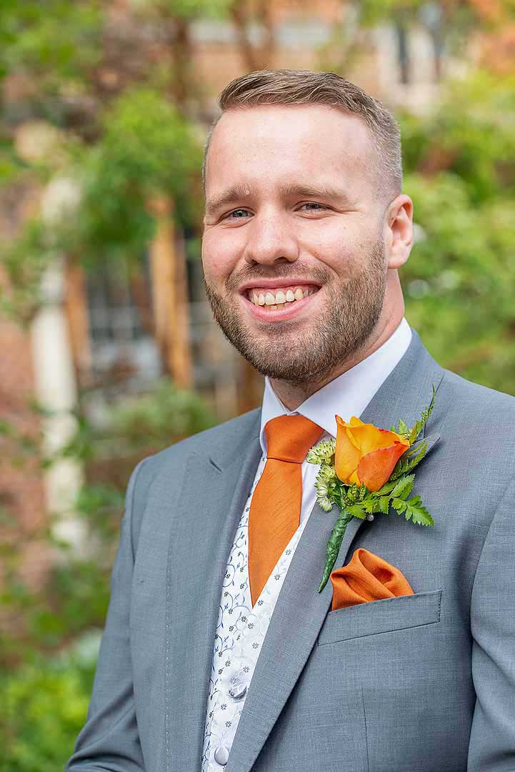 groom with grey suit, and orange tie, button hole and handkerchief