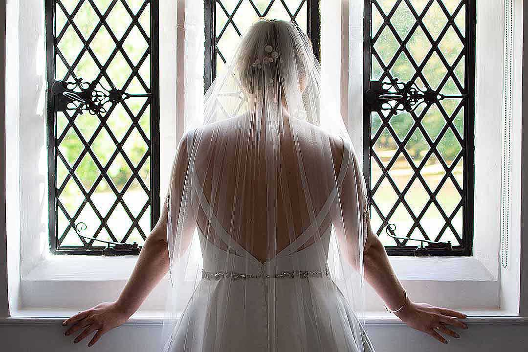 bride standing looking out of a window