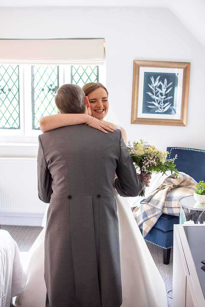 bride hugging her father in a bedroom