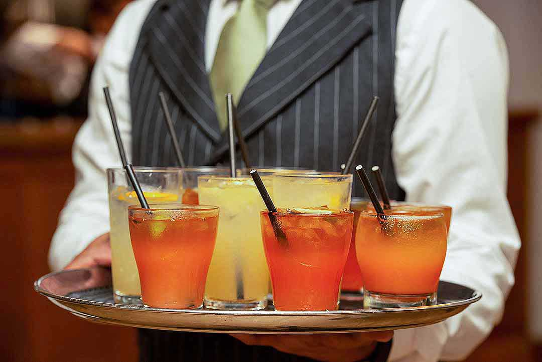 orange and yellow glasses held on a tray by a waiter in a grey pinstripe suit