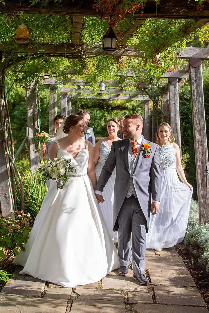 bride and groom followed by wedding party walking under a covered garden walkway