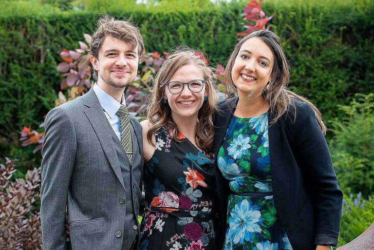 three wedding guests in a garden
