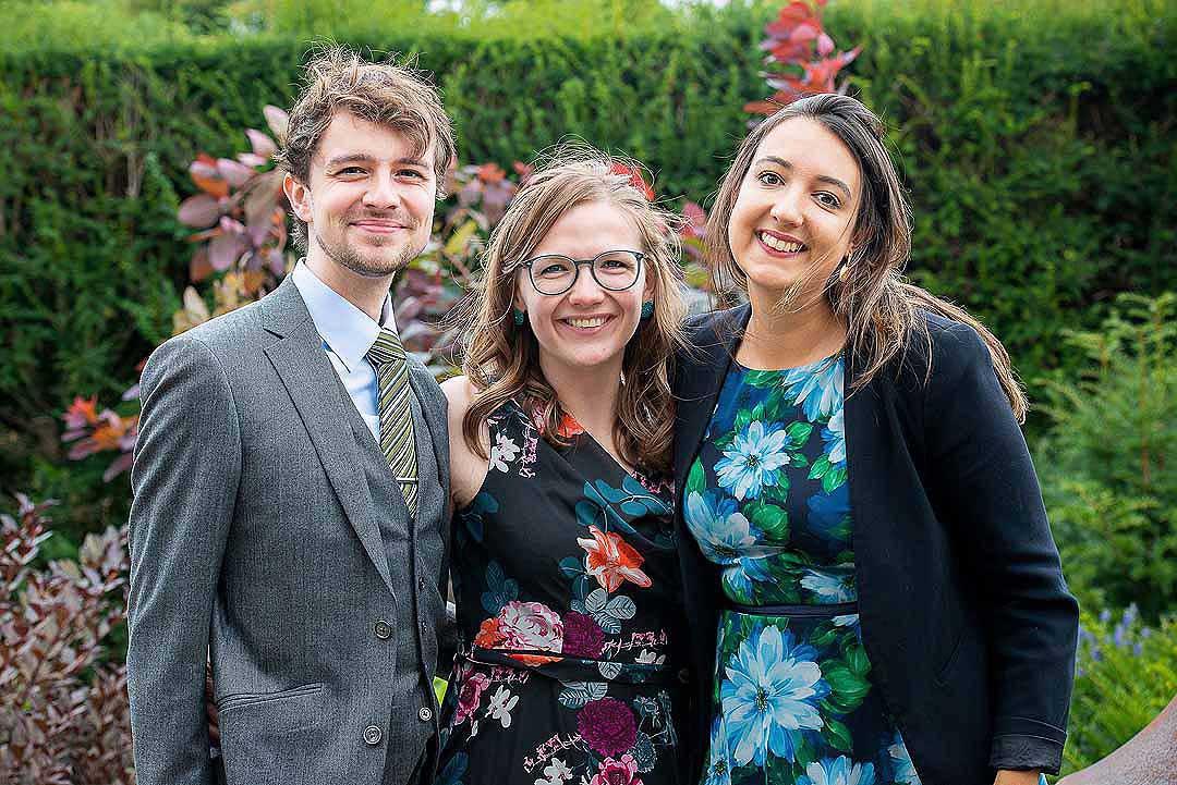 three wedding guests in a garden