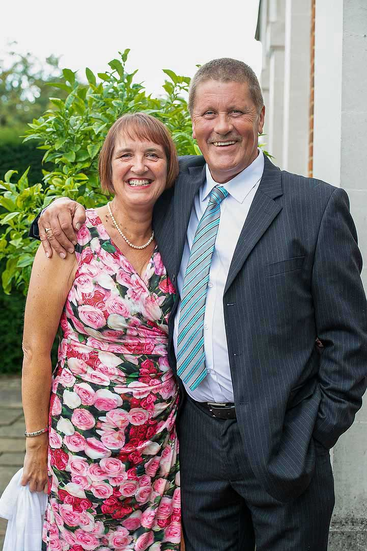 lady in a pink rose dress with a man in a grey suit with blue tie