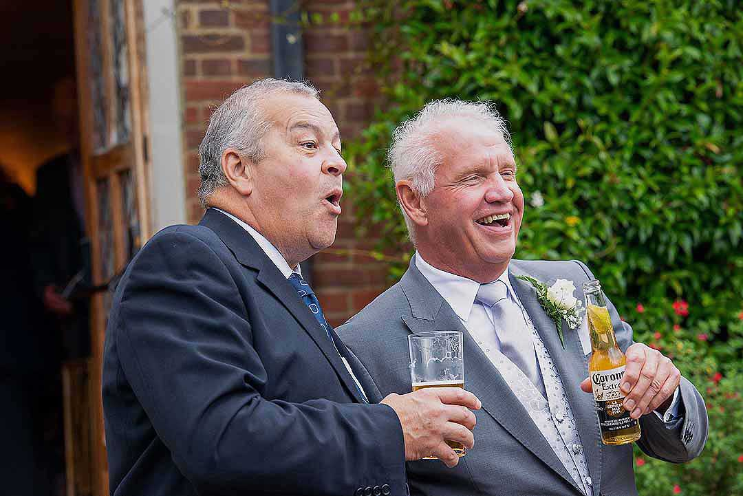 Two wedding guests drinking lager and laughing