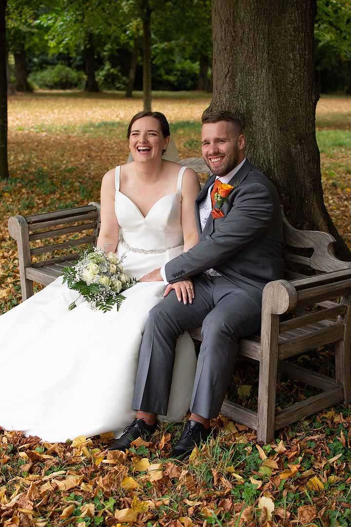 bride and groom sat on a bench with autumn leaves on the ground