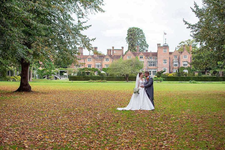 bride and groom outside with Great Fosters in the background