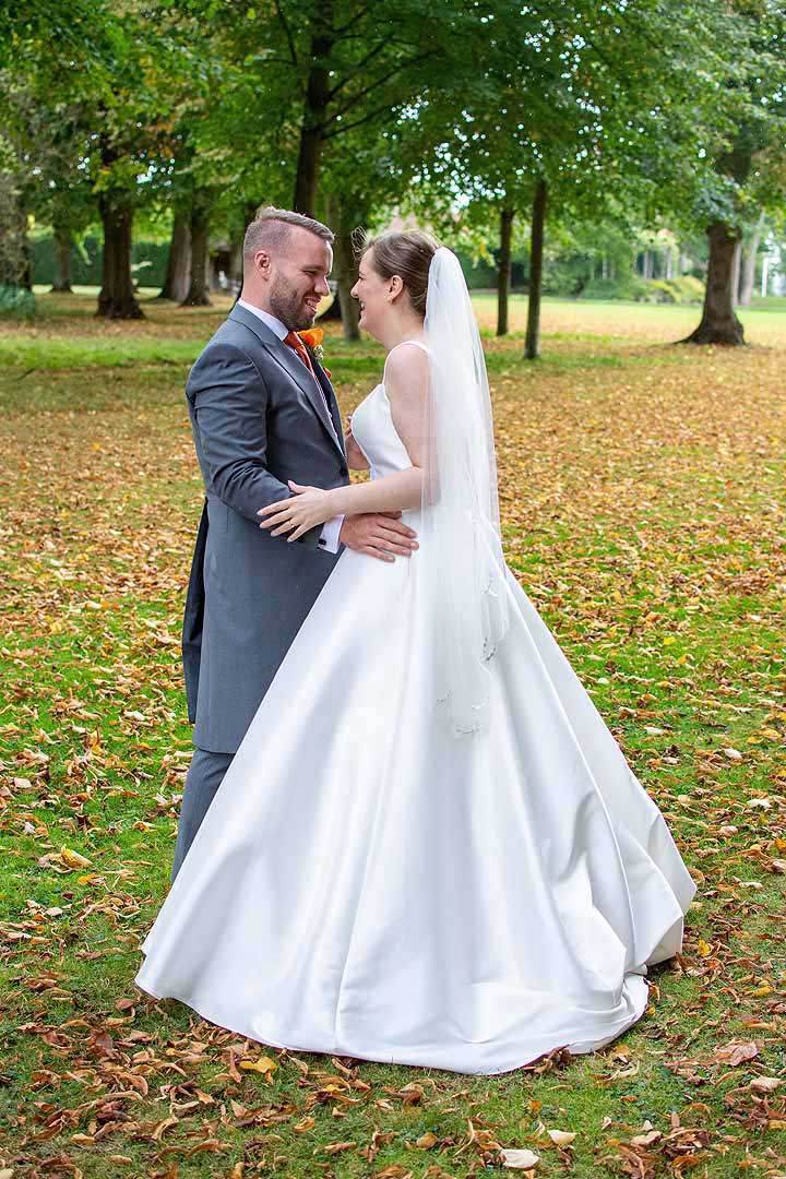 bride and groom outside with autumn leaves on the ground