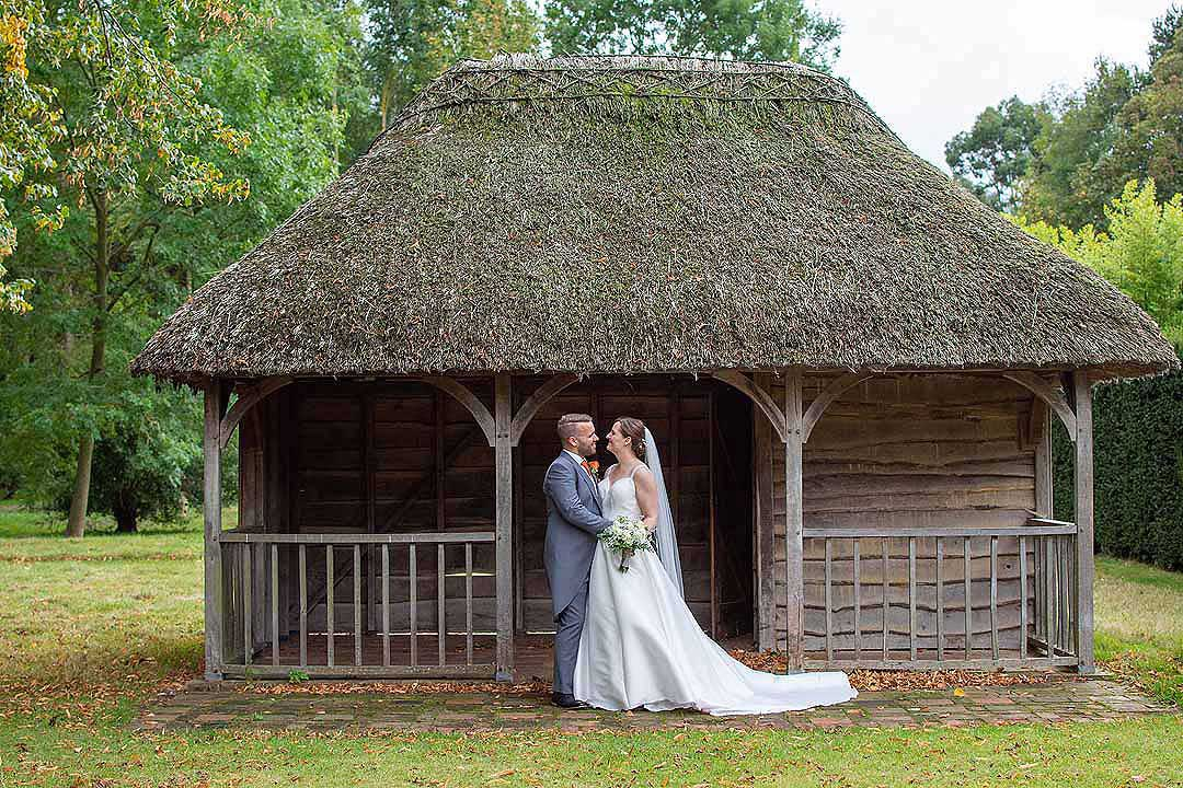 bride and groom standing outside a small thatched building in the garden