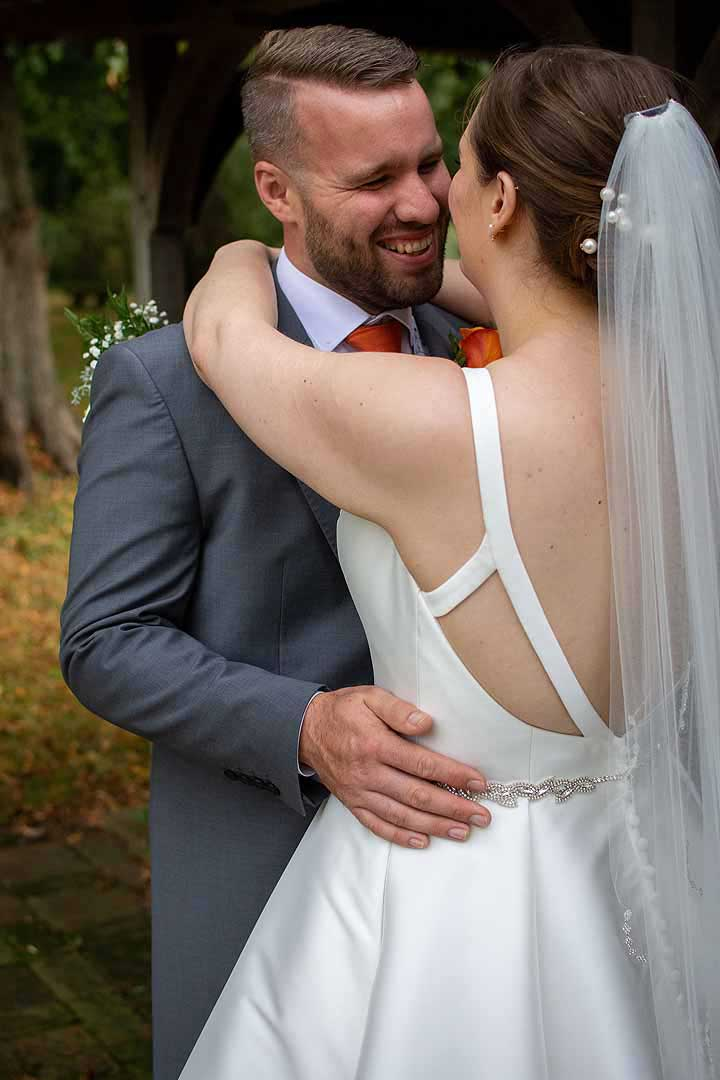 bride embracing groom in a grey suit