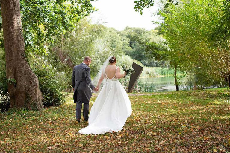Bride and groom walking to a lake with autumn leaves underfoot