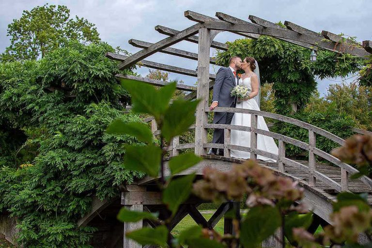 bride and groom standing on a Japanese bridge