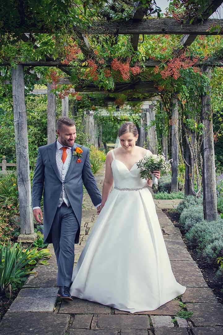 bride and groom walking in a garden with orange berries hanging down