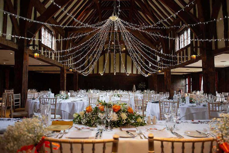 fairy lights over tables in the Tythe Barn at Great Fosters