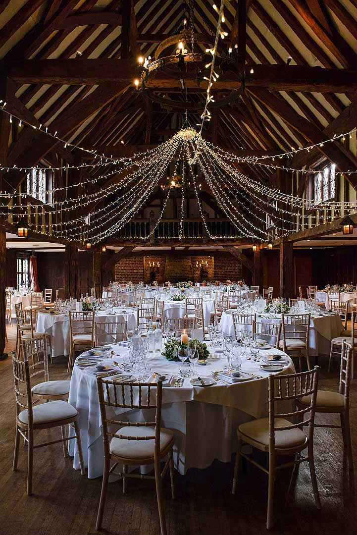 strung up fairy lights in the Tythe Barn at Great Fosters
