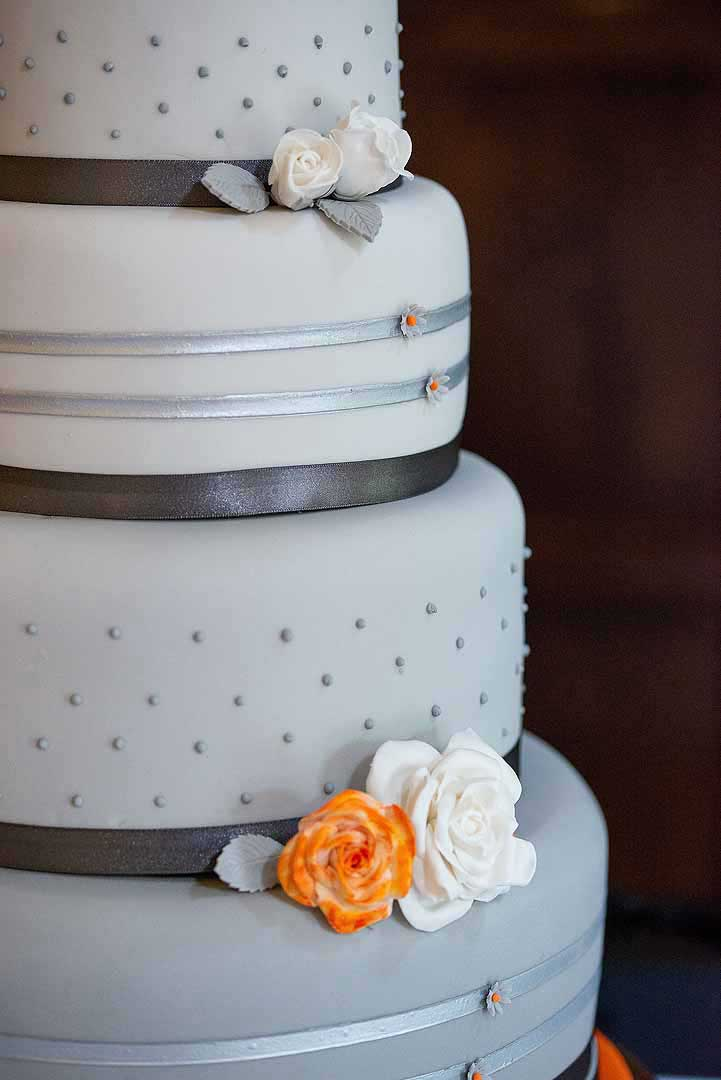 wedding cake details in white, orange and grey
