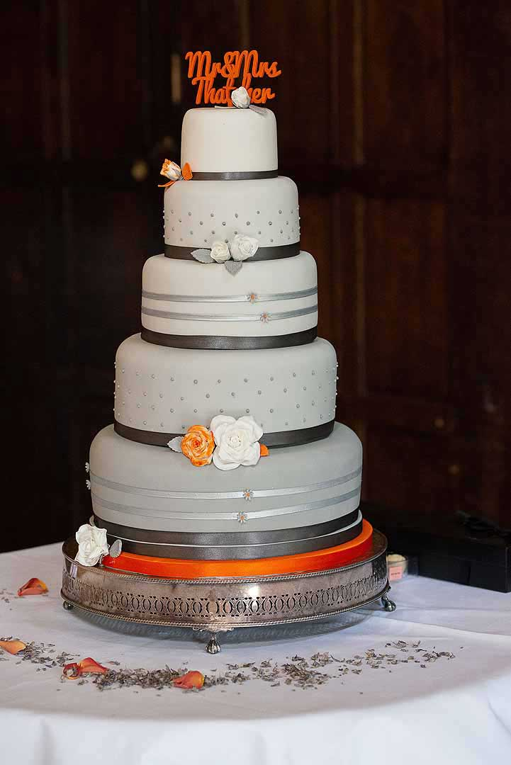 Five tiered wedding cake with white, orange and grey decoration
