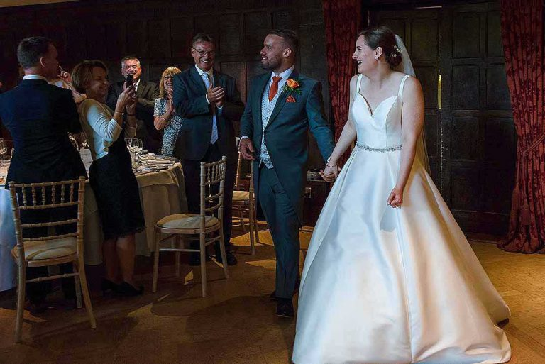 bride and groom making their entrance into the Tithe Barn at Great Fosters