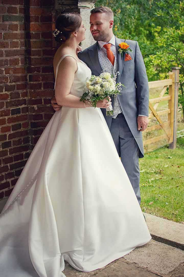 bride and groom standing next to a wall in a garden