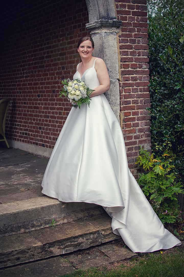 bride standing on some steps in a garden