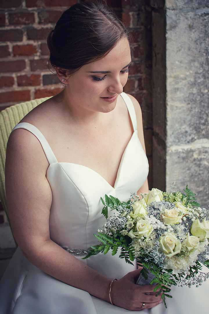 seated bride looking down at her flowers