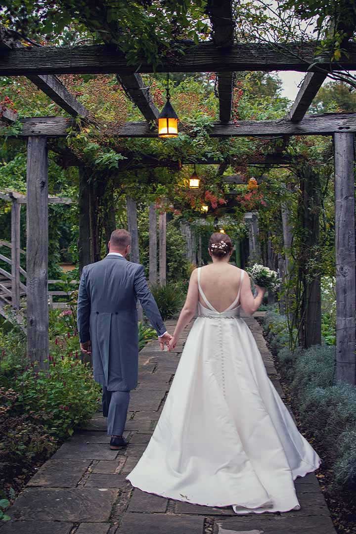 bride and groom walking down a garden path at dusk